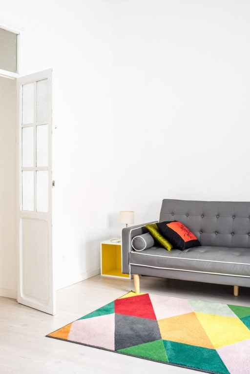 gray couch with white accent beside white wall